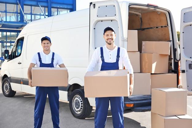 Uomini di consegna con scatole in movimento vicino all'automobile