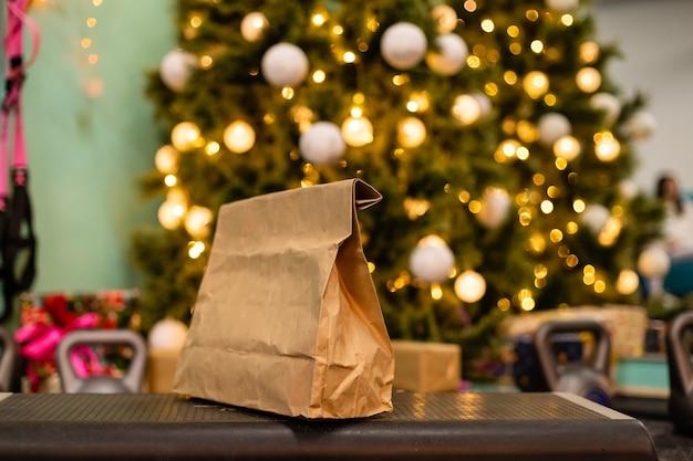 Pacchetto di consegna con cibo sano, peso e manubri sullo sfondo dell'albero di natale