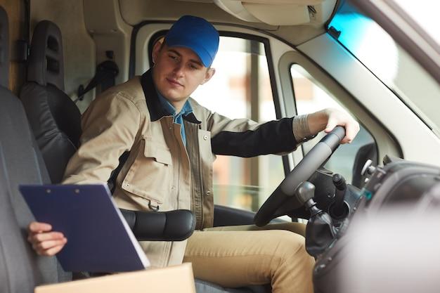 Addetto alle consegne che controlla l'indirizzo di consegna durante la guida del furgone