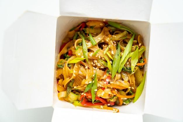 Consegna di cibo asiatico pronto. tagliatelle con verdure e frutti di mare in una scatola bianca. cena deliziosa. ordinare cibo per telefono o online. bastoncini di sushi.