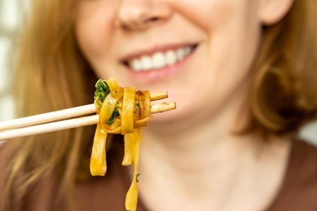 Consegna di cibo asiatico pronto. donna, ragazza mangia noodles con verdure e frutti di mare da bastoncini di sushi. cena deliziosa. ordinare cibo per telefono o online.