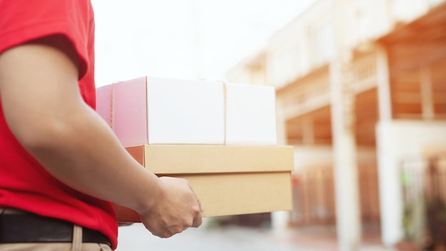 Corriere del servizio di consegna che suona il campanello di casa con le scatole in mano