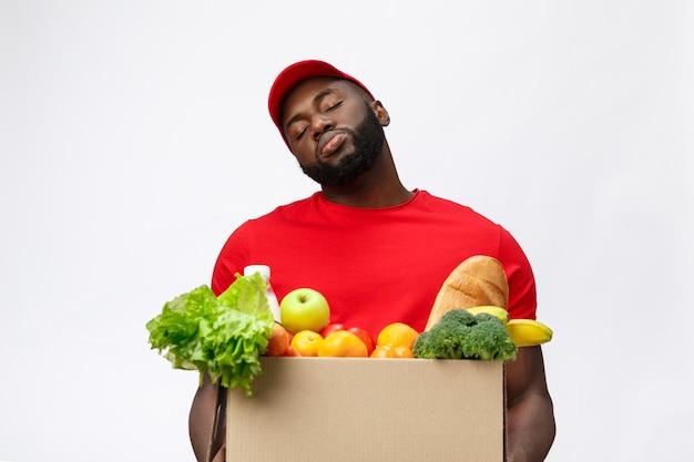 Servizio di consegna - bello afroamericano uomo di consegna che trasportano confezione di generi alimentari alimentari e bevande dal negozio.