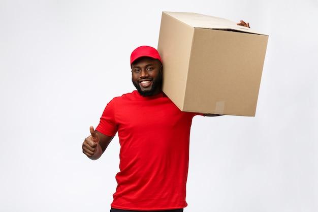 Servizio di consegna - bello uomo di consegna afroamericano che trasportano scatola del pacchetto.