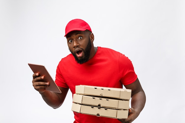 Servizio di consegna: uomo di consegna pizza africano bello che parla al cellulare con un'espressione facciale scioccante.