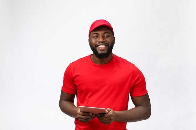 Servizio di consegna - ritratto dell'uomo di consegna afroamericano felice in panno rosso che tiene una compressa