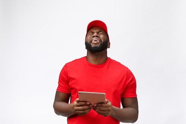 Servizio di consegna - ritratto di uomo di consegna afroamericano serio con tablet in espressione aggressiva sciocca e infelice.