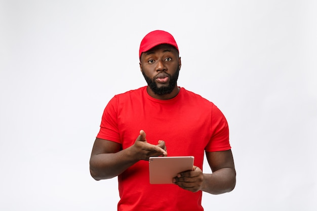 Servizio di consegna - ritratto di uomo di consegna afroamericano serio con tablet