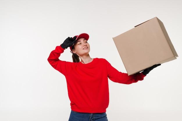 Donna di consegna che trasportano scatola di cartone isolata su bianco