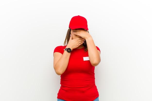 Donna delle consegne che copre il viso con entrambe le mani dicendo no alla telecamera! rifiutare le immagini o vietare le foto contro il bianco