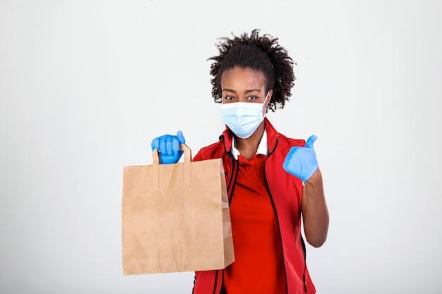 Donna di consegna che tiene il sacchetto di carta in guanti di gomma medicali e maschere che mostra pollice in su. copia spazio.