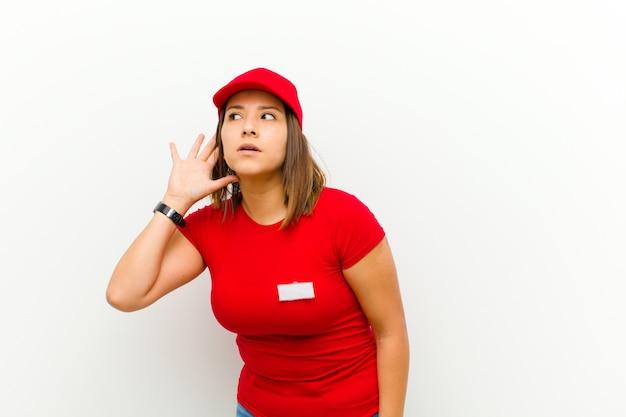 Donna di consegna che sembra seria e curiosa, ascoltando, cercando di ascoltare una conversazione segreta o gossip, intercettando su sfondo bianco