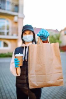 Donna di consegna in maschera protettiva e guanti con un sacchetto di cibo e caffè