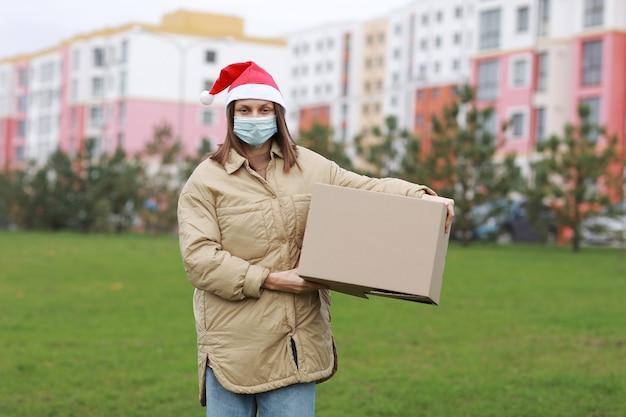 La donna delle consegne in un cappello rosso di babbo natale e una maschera protettiva medica tiene una grande scatola all'aperto. servizio coronavirus.
