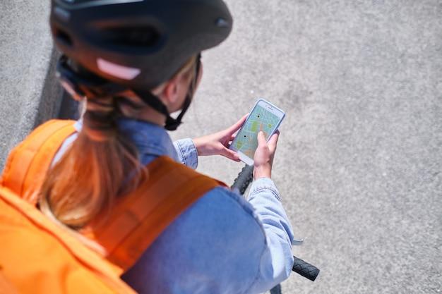 La donna delle consegne cerca sul suo smartphone una mappa con il percorso per la consegna a domicilio
