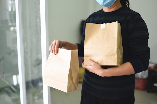 Donna di consegna che indossa la maschera per il viso e mano che tiene l'imballaggio alimentare servizio di consegna di cibo a casa