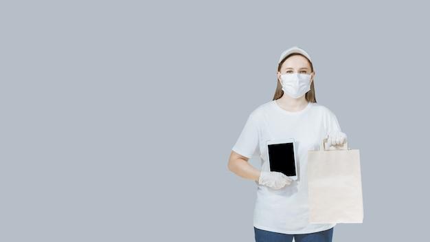 Donna delle consegne in uniforme bianca, in maschera e guanti,