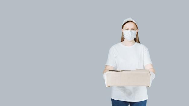 Donna di consegna con una scatola di corton in uniforme bianca che indossa una maschera e guanti