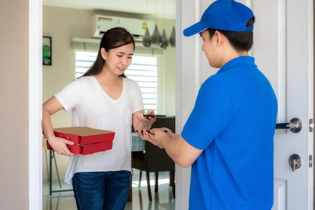 Consegna giovane uomo in uniforme blu sorriso e tenendo scatole di cibo in casa davanti