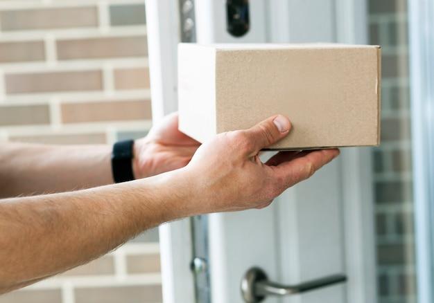 Il fattorino consegna la scatola di cartone al cliente alla porta di casa sua