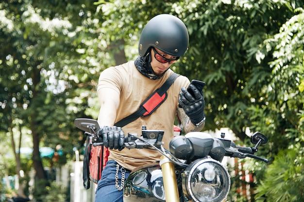 Fattorino in casco seduto sulla moto e controllando l'indirizzo del cliente tramite l'applicazione sullo smartphone