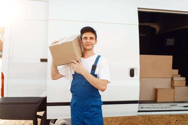 Fattorino in uniforme tiene la scatola di cartone in macchina, servizio di consegna.