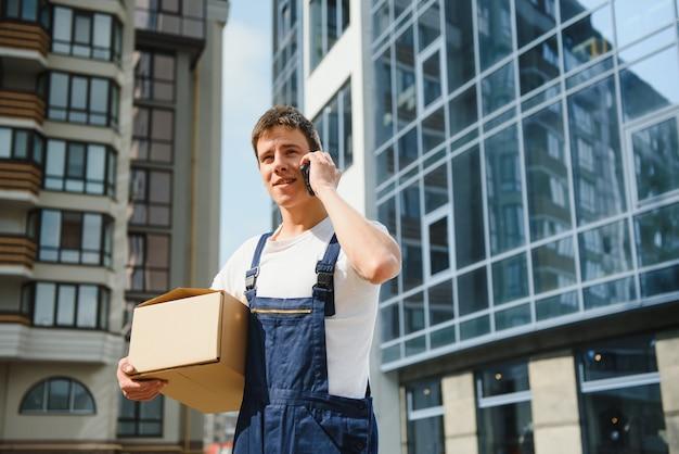 Il fattorino in uniforme tiene il pacco e il telefono