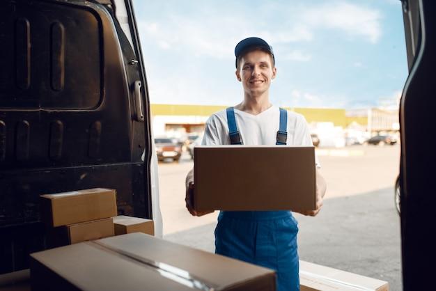 Fattorino in divisa scarica l'auto con i pacchi, servizio di consegna.