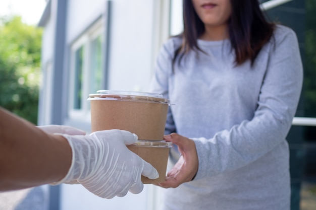 Il fattorino che indossa i guanti consegna scatole di cibo ai clienti. mano della donna che accetta la consegna di scatole di cibo dal mittente. concetto di consegna online