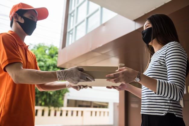 Il fattorino con maschera e guanti consegna la scatola della pizza al cliente femminile
