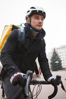 Fattorino che lavora in città, andando in bicicletta