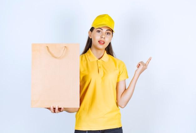 Fattorino in berretto giallo che tiene carta artigianale marrone e posa su bianco.
