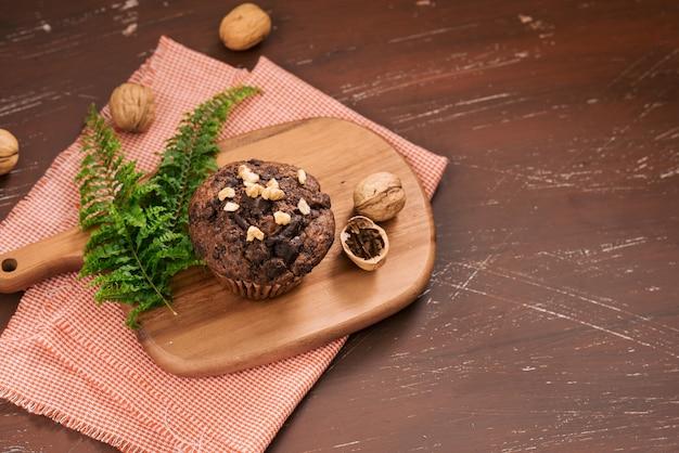 Delizioso muffin al cioccolato fatto in casa con noci sul tavolo. pronto a mangiare.