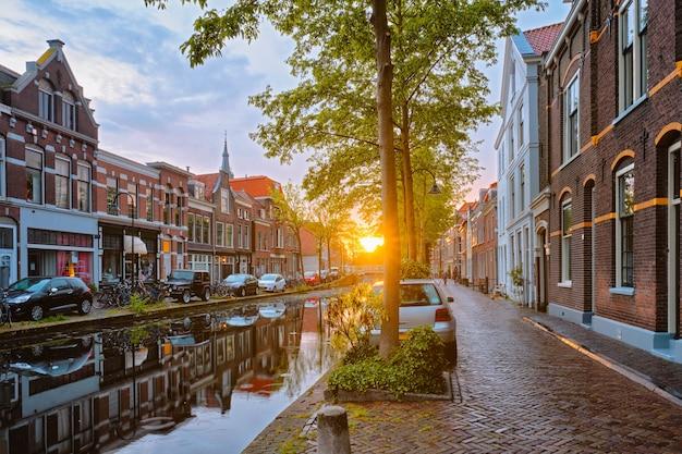 Delt canal con vecchie case e auto parcheggiate lungo il tramonto