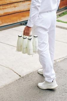 Delvery uomo che trasporta bottiglie di vetro all'ingresso del cliente