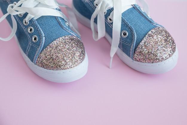 Scarpe per bambini in denim con lacci su sfondo rosa