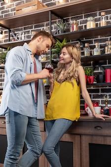 Vestiti di jeans. marito barbuto che indossa abiti in denim bevendo vino con la sua bella donna in cucina