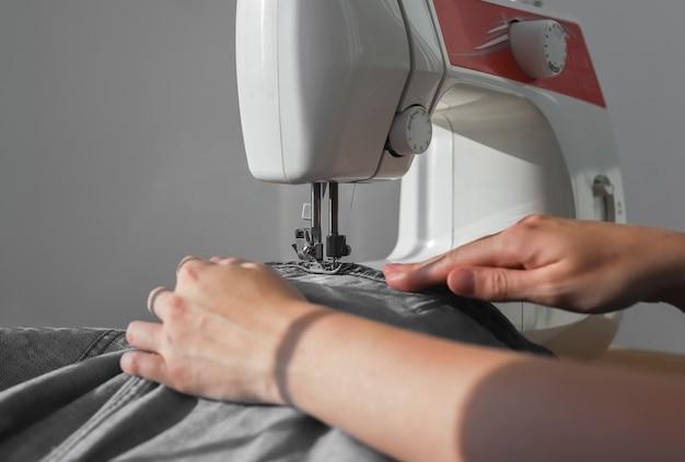 Tessuto denim sulla macchina da cucire da vicino le mani della ricamatrice al lavoro manuale