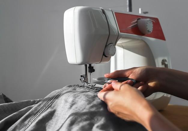 Panno dei jeans del denim sulle mani delle donne del primo piano della macchina da cucire al lavoro manuale