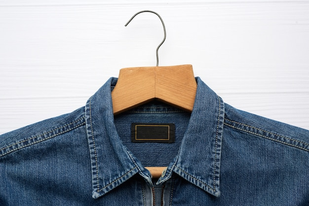 Camicia di jeans appesa al gancio di legno