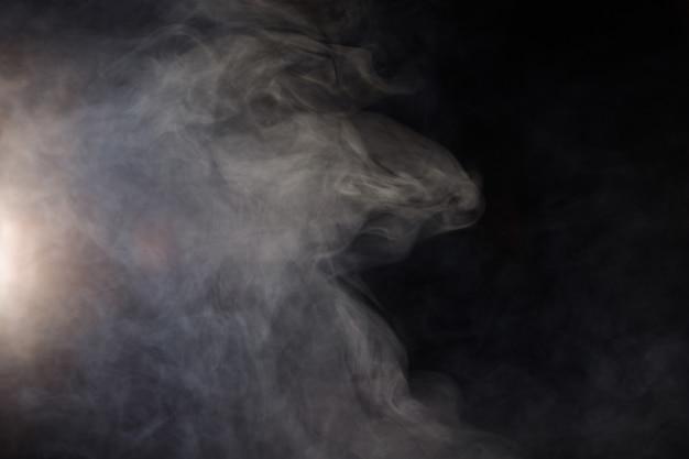 Dense soffici sbuffi di fumo bianco e nebbia su sfondo nero