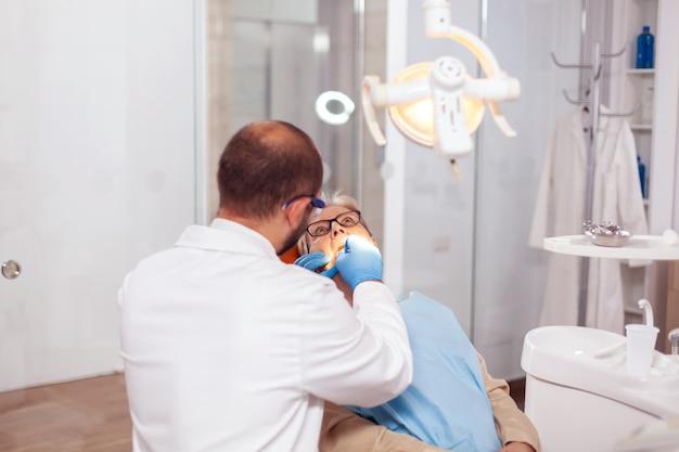 Denstis nel gabinetto che ripara il dente del paziente anziano in clinica odontoiatrica. paziente anziano durante la visita medica con il dentista in studio dentistico con attrezzatura arancione.