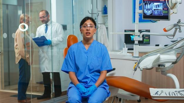 Assistente dentale che guarda l'obbiettivo che parla con i pazienti dell'igiene dentale. stomatologo parlando in webcam seduto su una sedia in clinica stomatologica con medico in background che lavora al computer