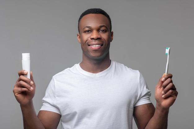 Igiene dentale. giovane adulto contento dalla pelle scura con un sorriso bianco come la neve con spazzolino da denti e pasta tra le mani su sfondo chiaro