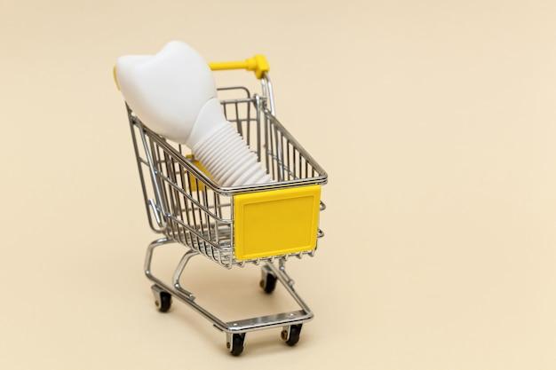 Impianto dentale in un carrello della spesa in metallo su sfondo beige