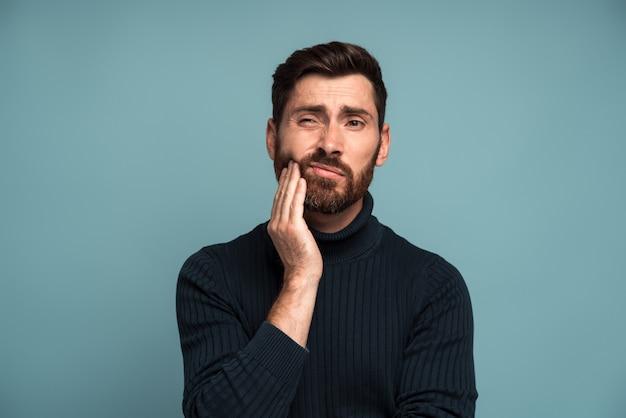 Problemi dentali. ritratto di un uomo malsano che preme guancia dolorante, che soffre di mal di denti acuto, malattia parodontale, cavità o dolore alla mandibola. colpo dello studio dell'interno isolato su fondo blu