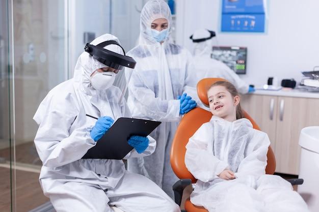 Specialista dentale che tiene appunti durante l'epidemia di coronavirus e bambina seduta su una sedia. stomatologo durante il covid19 che indossa una tuta in dpi facendo la procedura dei denti del bambino seduto sulla sedia.