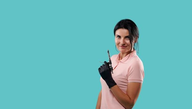 Siringa dentale per anestesia intraligamentare nelle mani in guanti medicali sterili neri di un giovane dentista in piedi isolato su sfondo blu