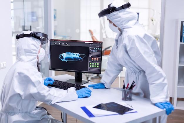 Gruppo odontoiatrico in tuta dpi che esamina i raggi x dei denti del paziente. specialista medico che indossa indumenti protettivi contro il coronavirus durante l'epidemia globale guardando la radiografia nello studio dentistico.