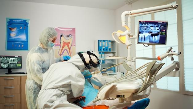 Odontotecnico in equipaggiamento protettivo che accende la lampada per l'esame del bambino paziente durante l'epidemia di covid-19. equipe medica che parla con la madre che indossa visiera, tuta, maschera e guanti
